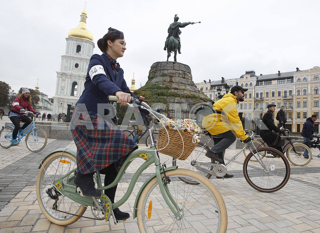 The girl in a plaid skirt and a hat edit together with other participants on a bicycle — Image 38964