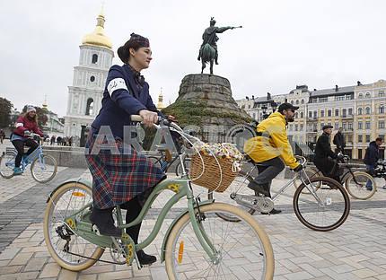 Девушка в клетчатой юбке и шляпке едит вместе с другими участниками на велосипеде
