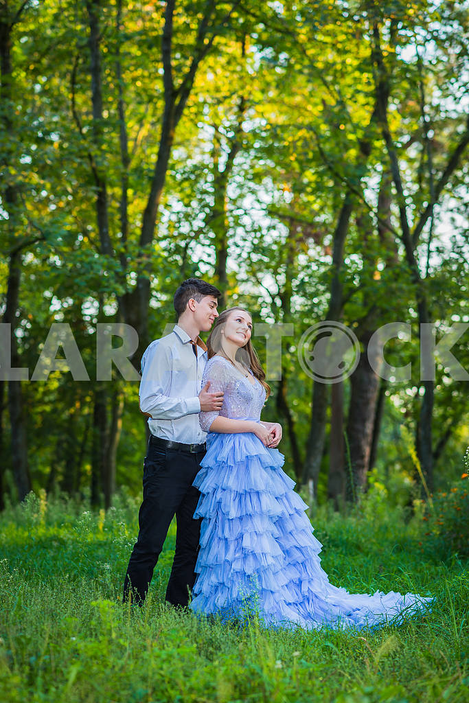 A love story couple, in love, together in the forrest park, girl in a beautiful violet dress, sunny evening, summer, thematic wedding shooting, frill dress — Image 39059