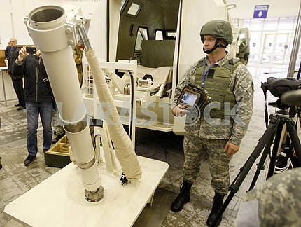 A man in uniform stands near a mobile mortar complex