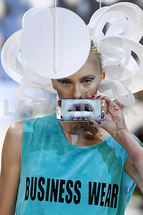 A model holds a phone and demonstrates outfit by Ukrainian designer Alexey Zalewskiy