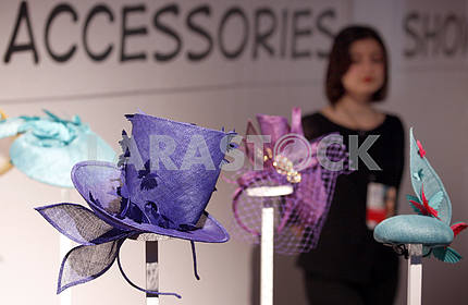 A visitor stands near designer hats
