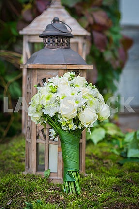 The wedding bouquet for the bride made of white roses and green chrysanthemum  Vintage wooden lantern and moss on the background