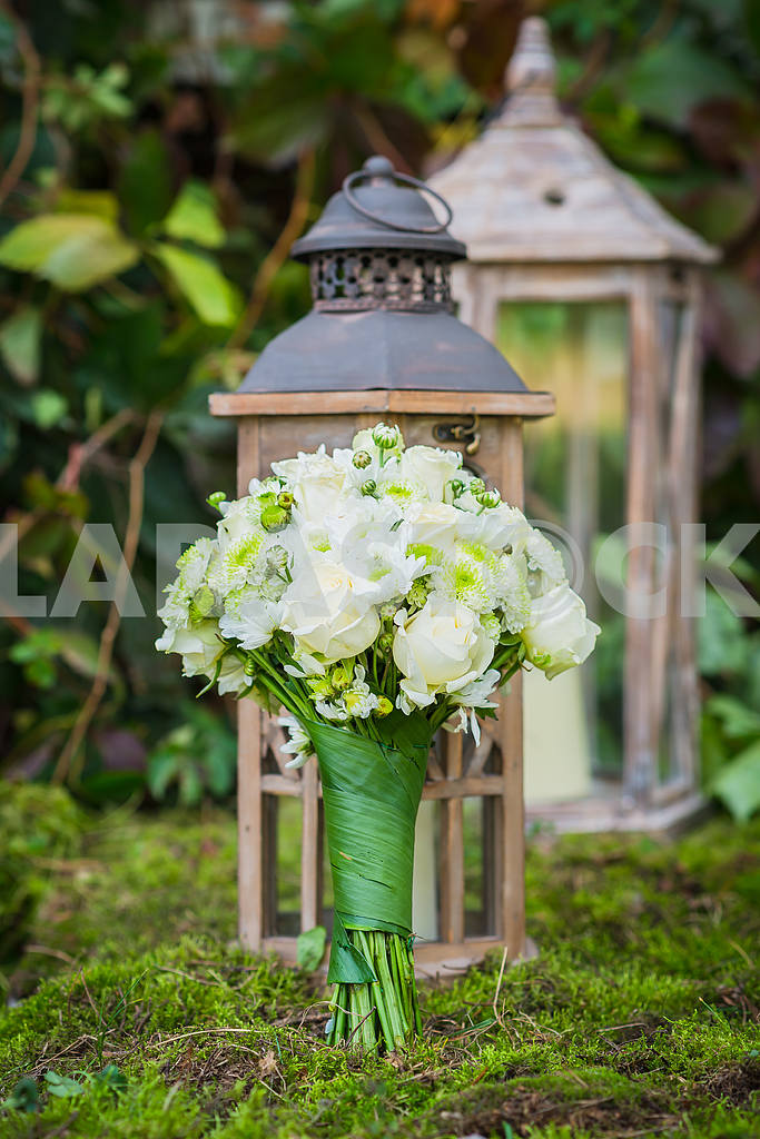 The wedding bouquet for the bride made of white roses and green chrysanthemum  Vintage wooden lantern and moss on the background — Image 39229