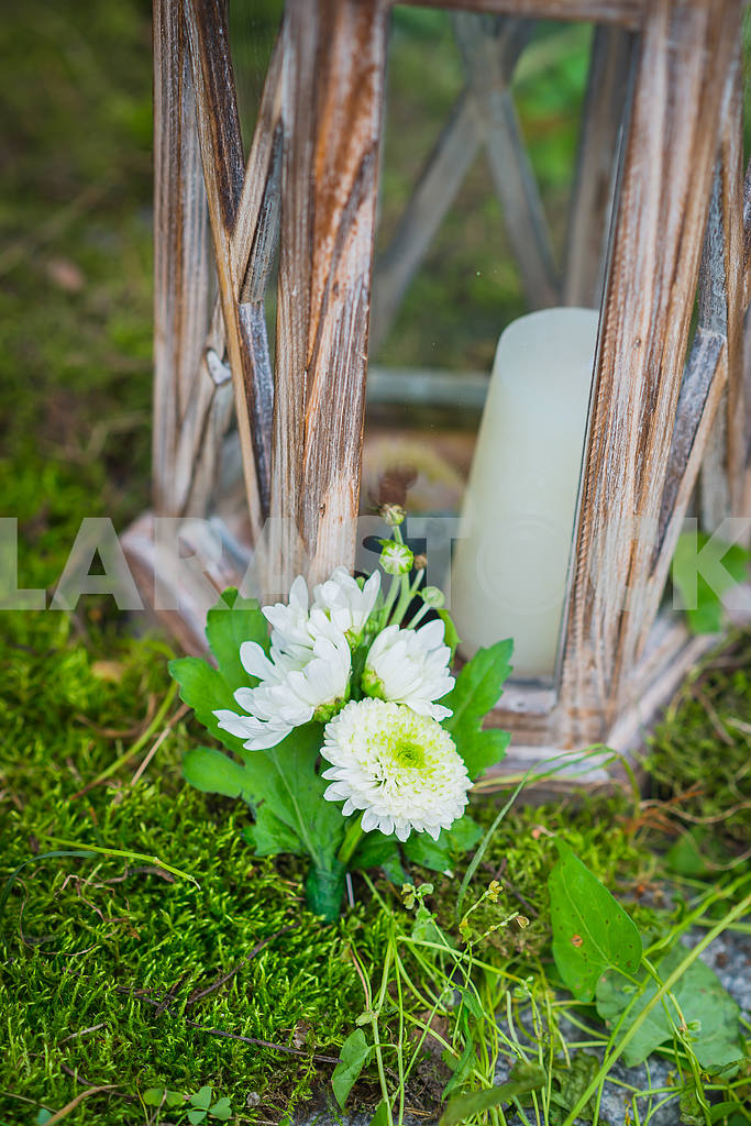 The wedding boutonniere for the groom made of white and green chrysanthemum  Vintage wooden lantern and moss on the background and a candle — Image 39230