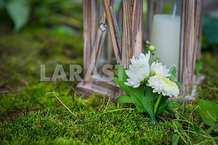 Свадебная бутоньерка для жениха из белых и зеленых хризантем Старинные деревянные фонарь и мох на заднем плане и свеча