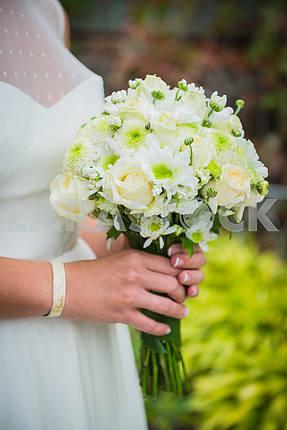Невеста, держащая свадебный букет в ее руках из белых роз и зеленых хризантем