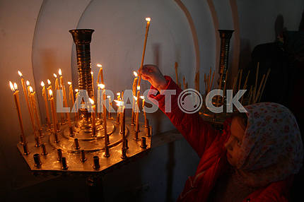 A woman puts a candle. Feast of the Intercession of the Holy Virgin