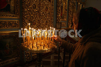 Elderly woman puts a candle
