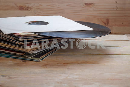 Vinyl record with copy space in front of a collection albums dummy titles, vintage process