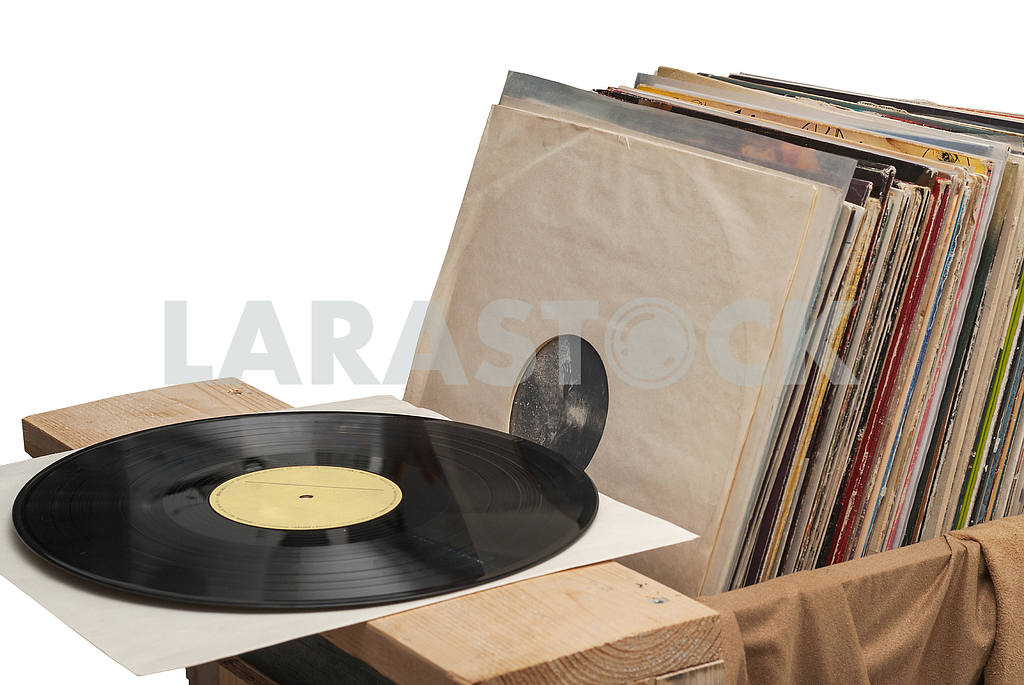 Retro styled image of a collection of old vinyl record lp's with sleeves on a wooden background. Copy space — Image 39927