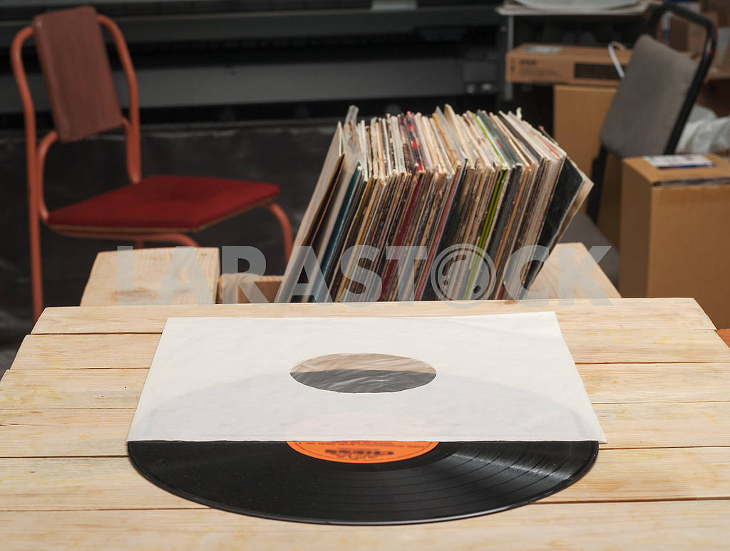 Retro styled image of a collection of old vinyl record lp's with sleeves on a wooden background. Copy space — Image 39937