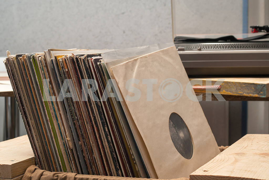 Retro styled image of a collection of old vinyl record lp's with sleeves on a wooden background. Copy space — Image 39970
