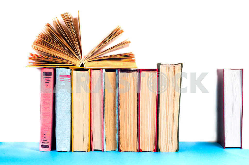 Open book, stack of colorful hardback books on light table. Back to school. Copy space for text — Image 41842