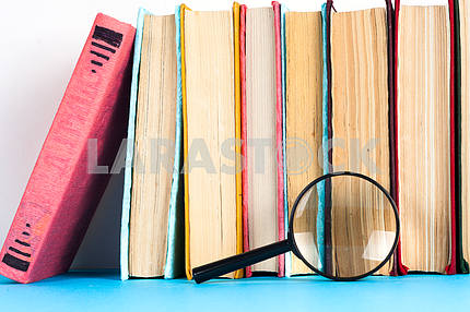 Composition with open book and magnifying glass. Back to school, copy space. Education background.