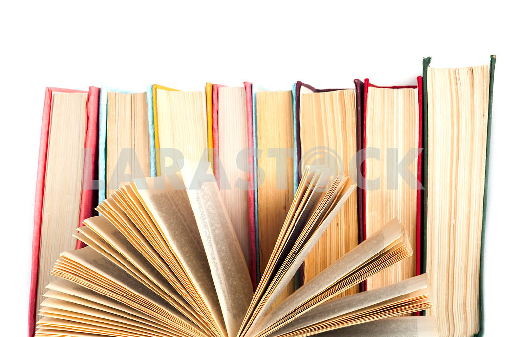 Open book, stack of colorful hardback books on light table. Back to school. Copy space for text — Image 41852