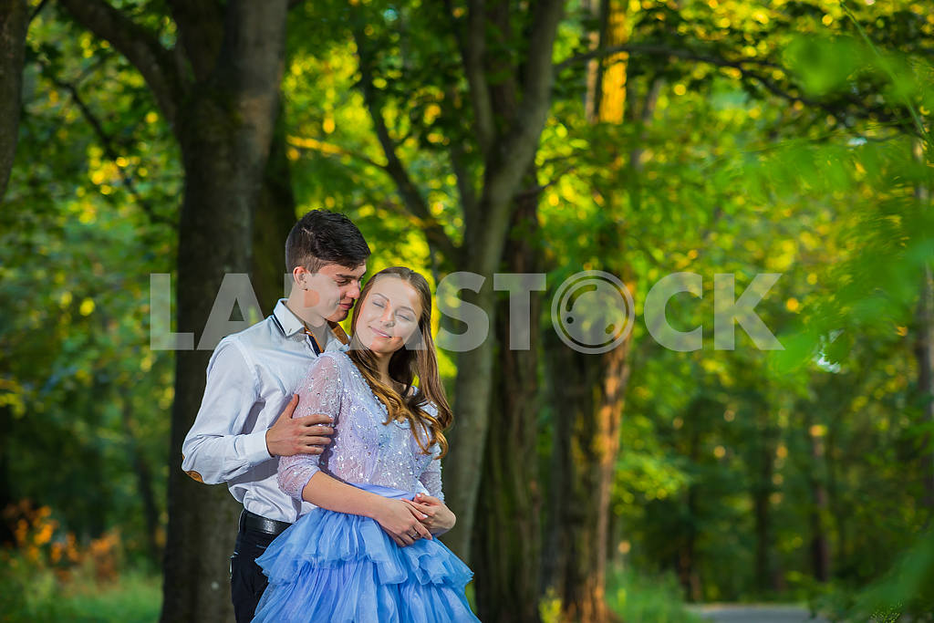 A love story couple, in love, together in the forrest park,  girl in a beautiful violet dress, sunny evening, summer, holding each other — Image 42333