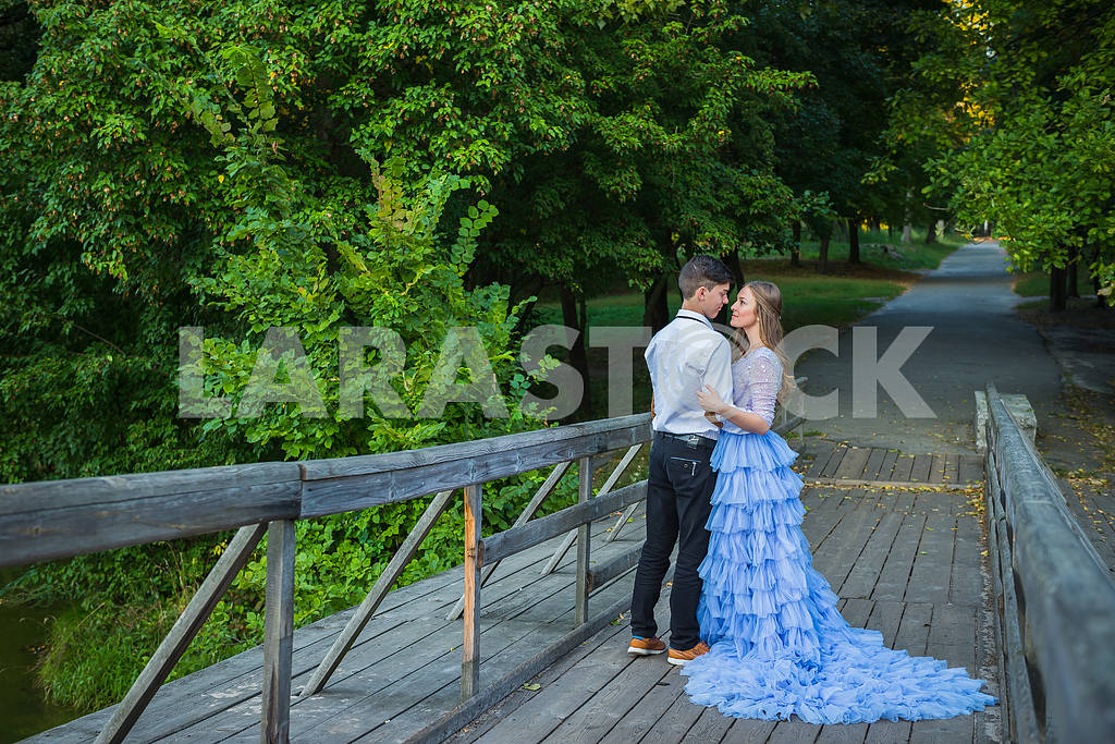 A love story couple, in love, together in the forrest park, on the wooden bridge,  girl in a beautiful violet dress, sunny evening, summer — Image 42335