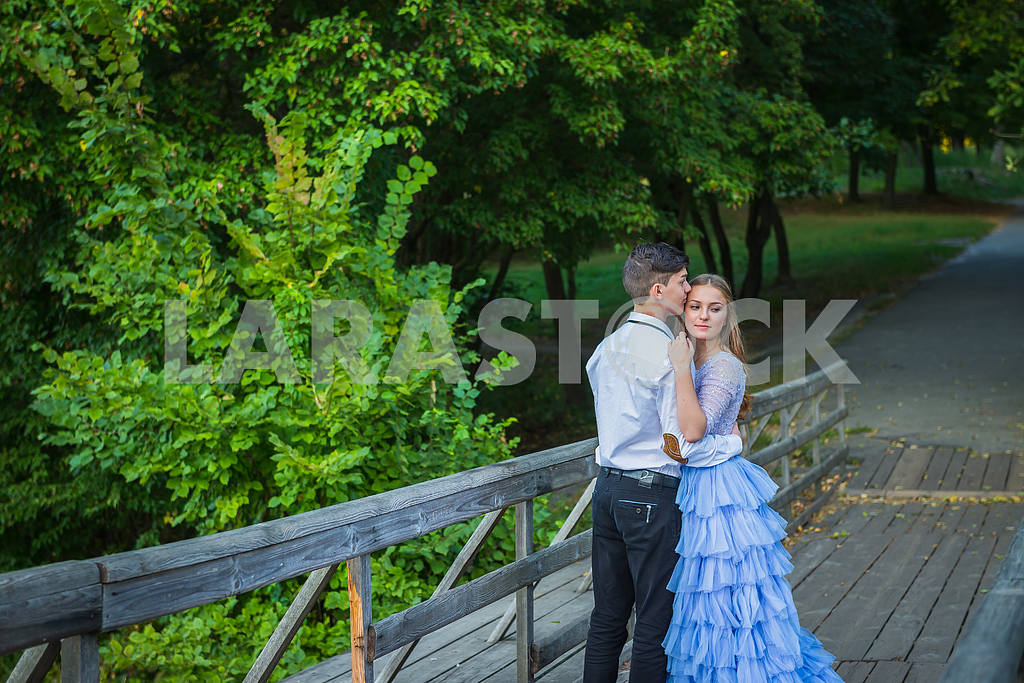 A love story couple, in love, together in the forrest park, on the wooden bridge,  girl in a beautiful violet dress, sunny evening, summer — Image 42336