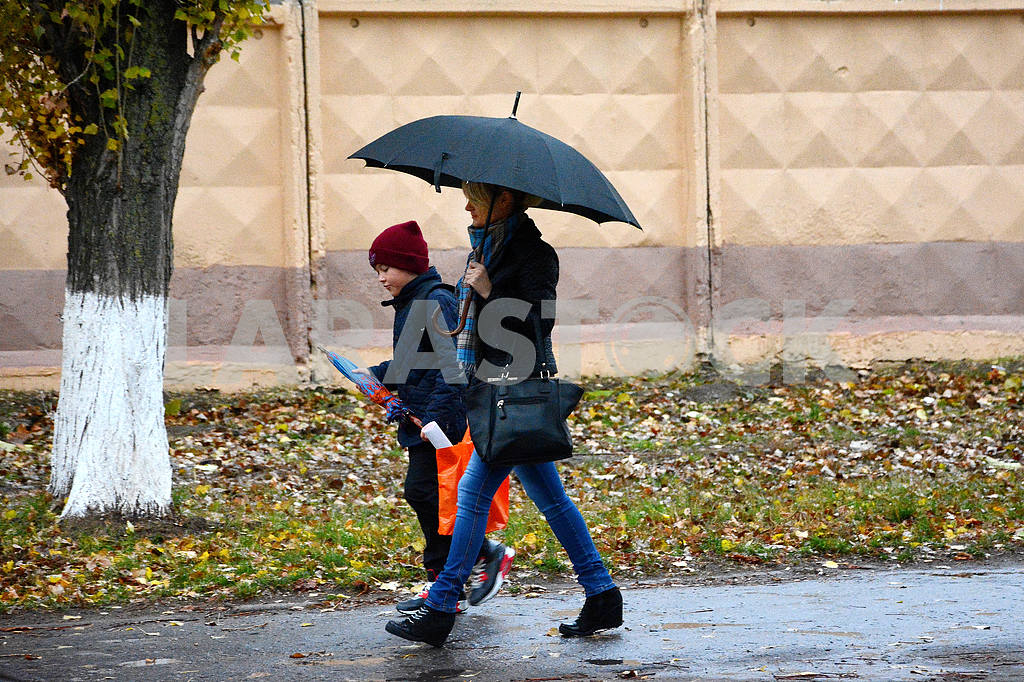 A woman and a boy go under an umbrella — Image 42388