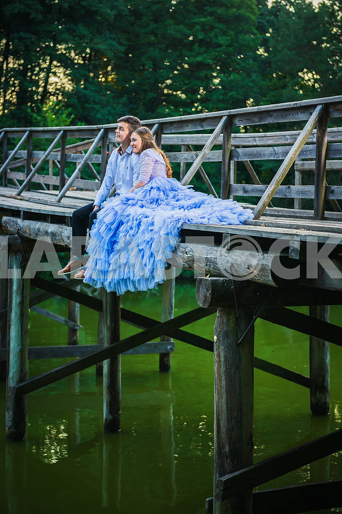 A love story couple, in love, together in the forrest park, sitting on the end of  wooden bridge, girl in a beautiful violet dress, sunny evening, summer, green water on the background — Image 42667