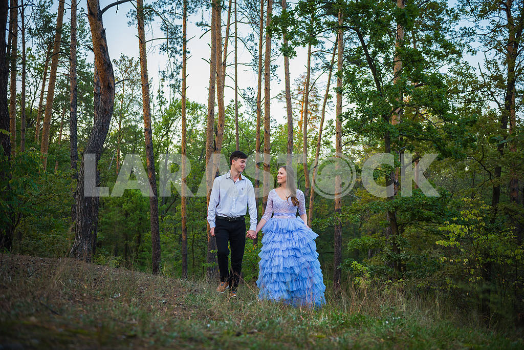 A love story couple, in love, together in the forrest park, girl in a beautiful violet dress,  evening, summer, holding each other, near the pine tree walking — Image 42758
