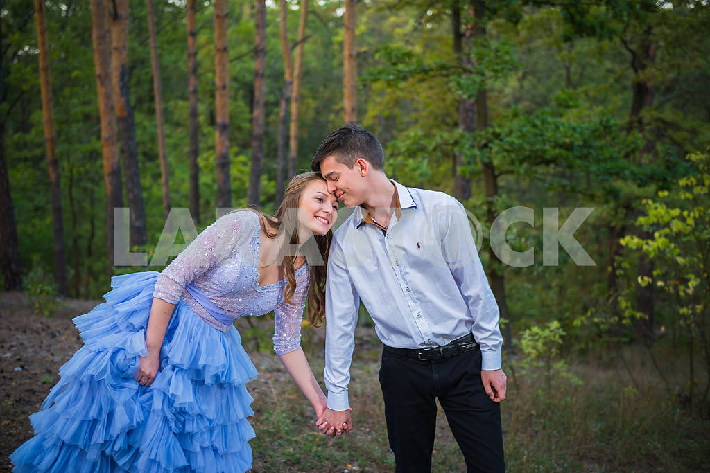 A love story couple, in love, together in the forrest park, girl in a beautiful violet dress,  evening, summer, holding each other, near the pine tree — Image 42759