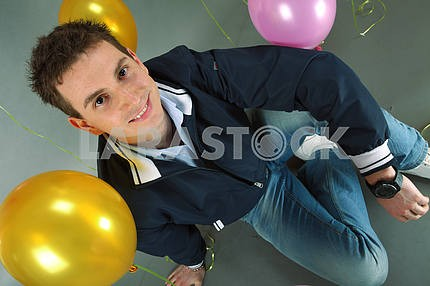 Young smiling man against of balloons