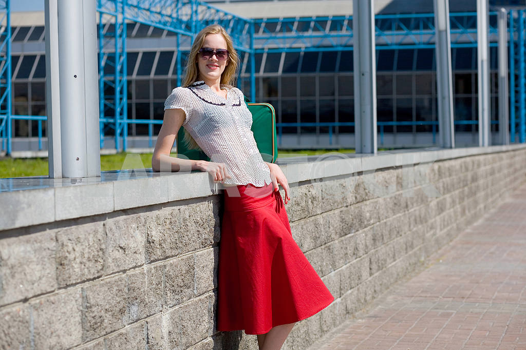 Smiling sexy blonde girl wearing red skirt. Near green bag. — Image 4436