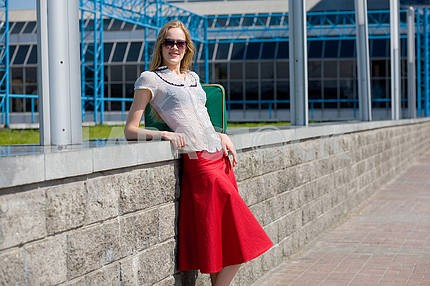 Smiling sexy blonde girl wearing red skirt. Near green bag.