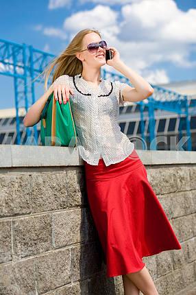 Улыбаясь сексуальный блондинка разговаривает по телефону . Рядом зеленый мешок .