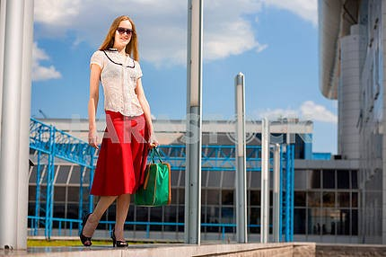 Улыбаясь сексуальный блондинка носить красную юбку с зеленой сумкой . В