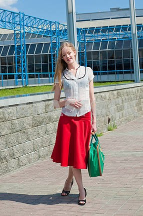 Smiling sexy blonde girl wearing red skirt with a green bag. In