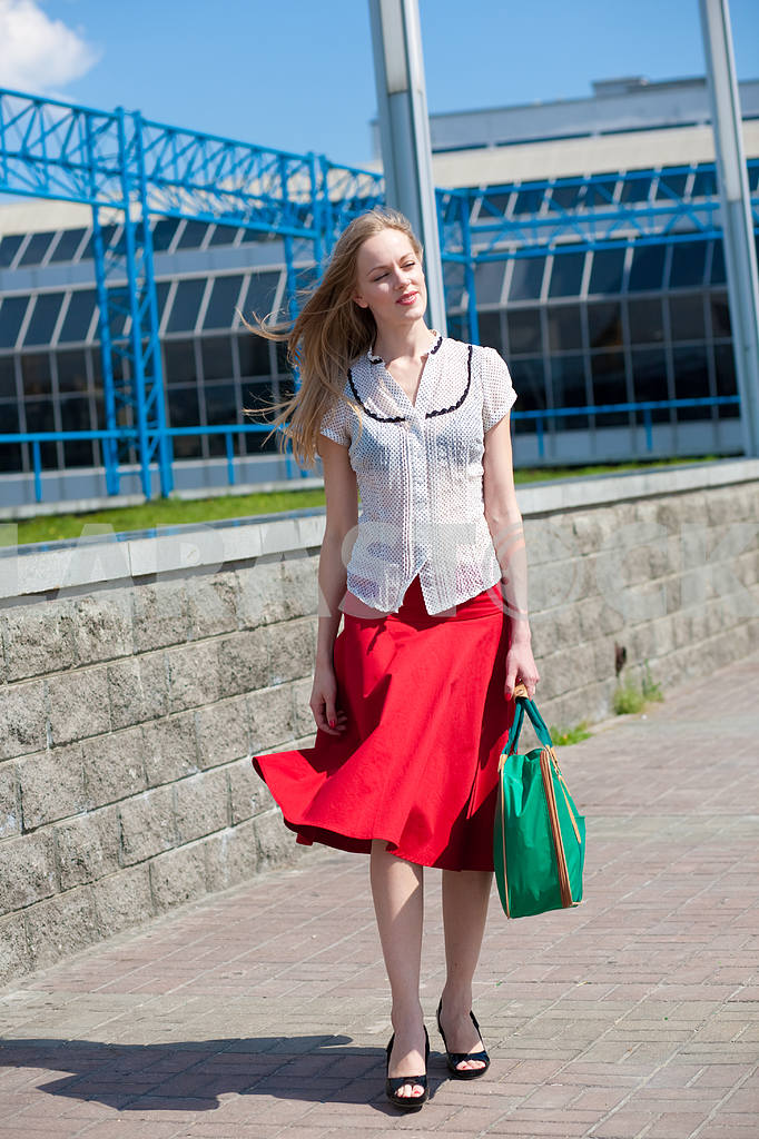 Smiling sexy blonde girl wearing red skirt with a green bag. In  — Image 4447