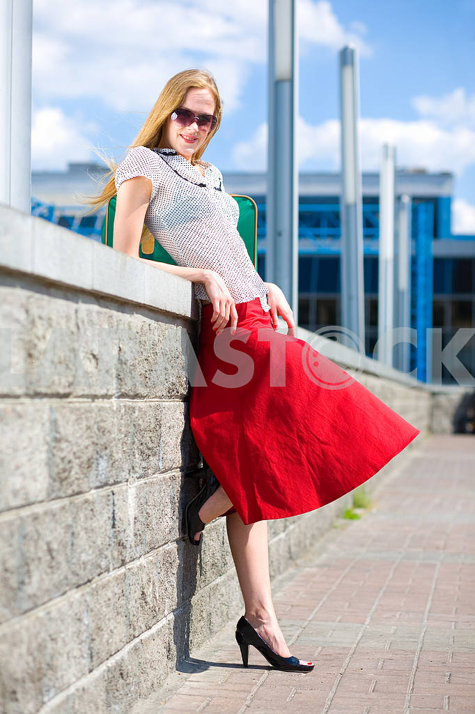 Smiling sexy blonde girl wearing red skirt. In all growth. Near  — Image 4448