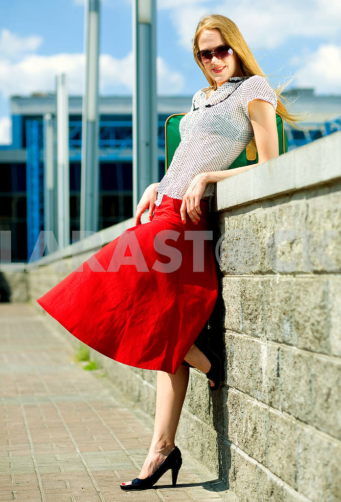 Smiling sexy blonde girl wearing red skirt. In all growth. Near  — Image 4449