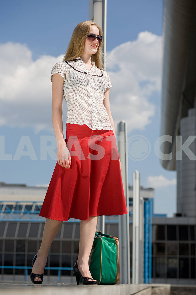 Smiling sexy blonde girl with green suitcase — Image 4453