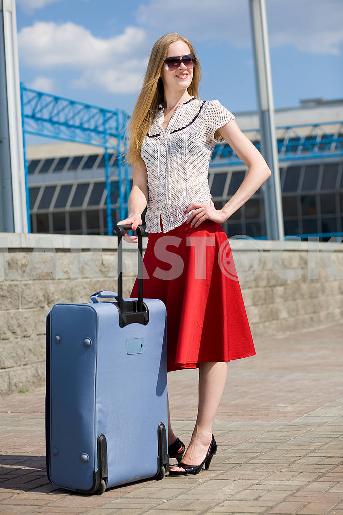 Smiling sexy blonde girl with blue suitcase — Image 4457