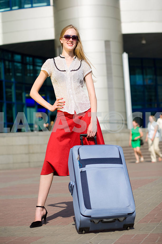 Smiling sexy blonde girl with blue suitcase — Image 4464