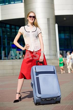 Улыбаясь секси блондинка девушка с голубой чемодан