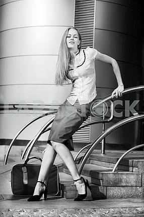 Beautiful young woman with a suitcase against the backdrop of th