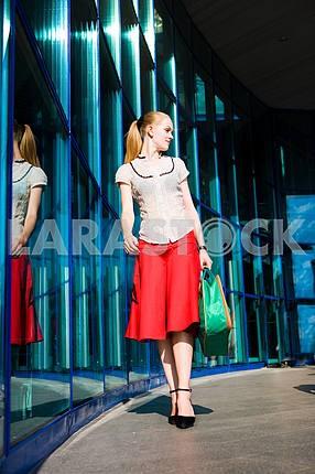Красивая девушка с чемоданом на фоне в стати