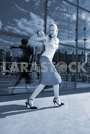 Young woman, blond, runs against the backdrop of the station. In