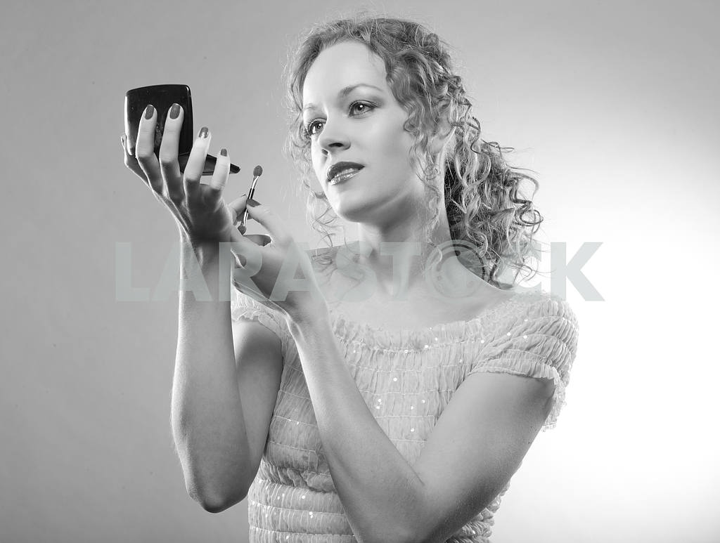 Pretty woman applying make-up with powder. Black And White photo — Image 4489