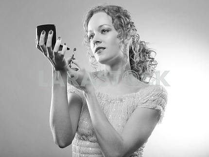 Pretty woman applying make-up with powder. Black And White photo