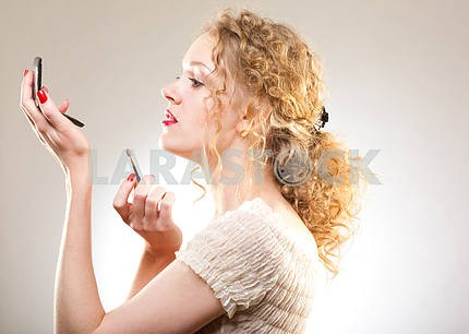 Pretty woman applying make-up with powder