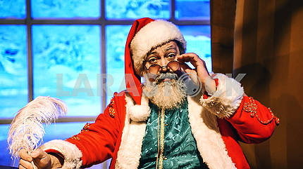 Дед мороз сидит в кресле и рукой поддерживает очки.