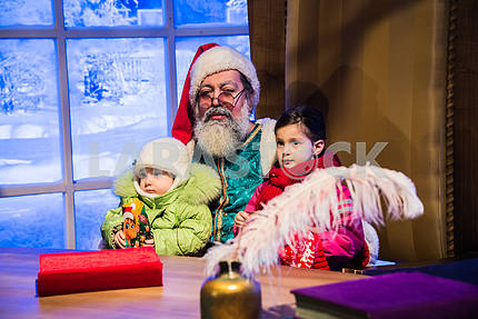 Santa Claus holding a girl and a boy in his arms in his chair.