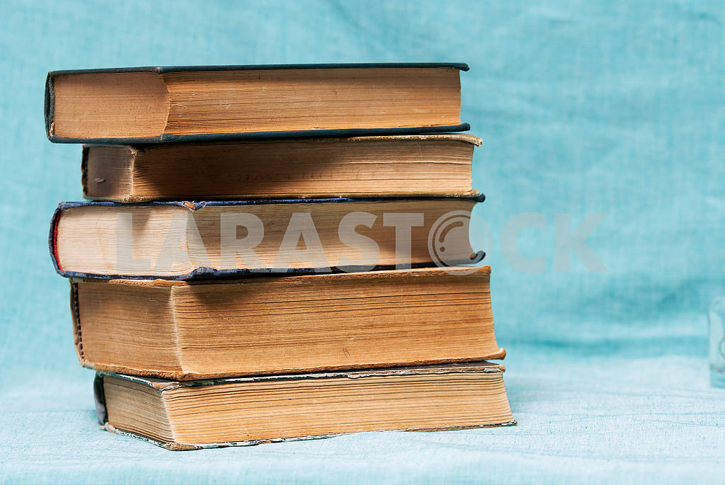 Stack of hardback books on blue cloth. Back to school. Copy space — Image 45327
