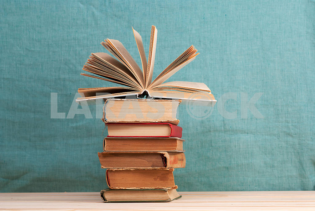 Stack of hardback books on blue cloth. Back to school. Copy space — Image 45338